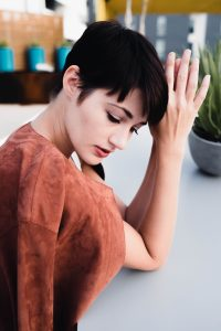 Beautiful woman sits at a desk, thinking about removing name from a title loan