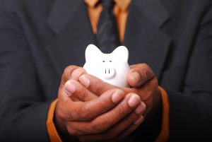 Man in a suit holds a piggy bank