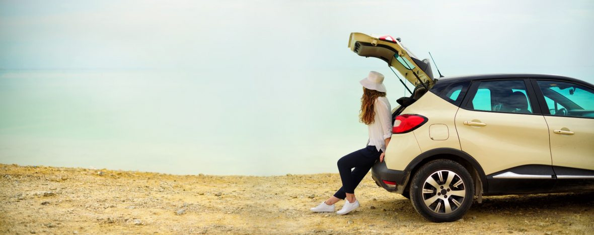 Beautiful young woman sits on the back trunk of her car's hatch back on the beach.