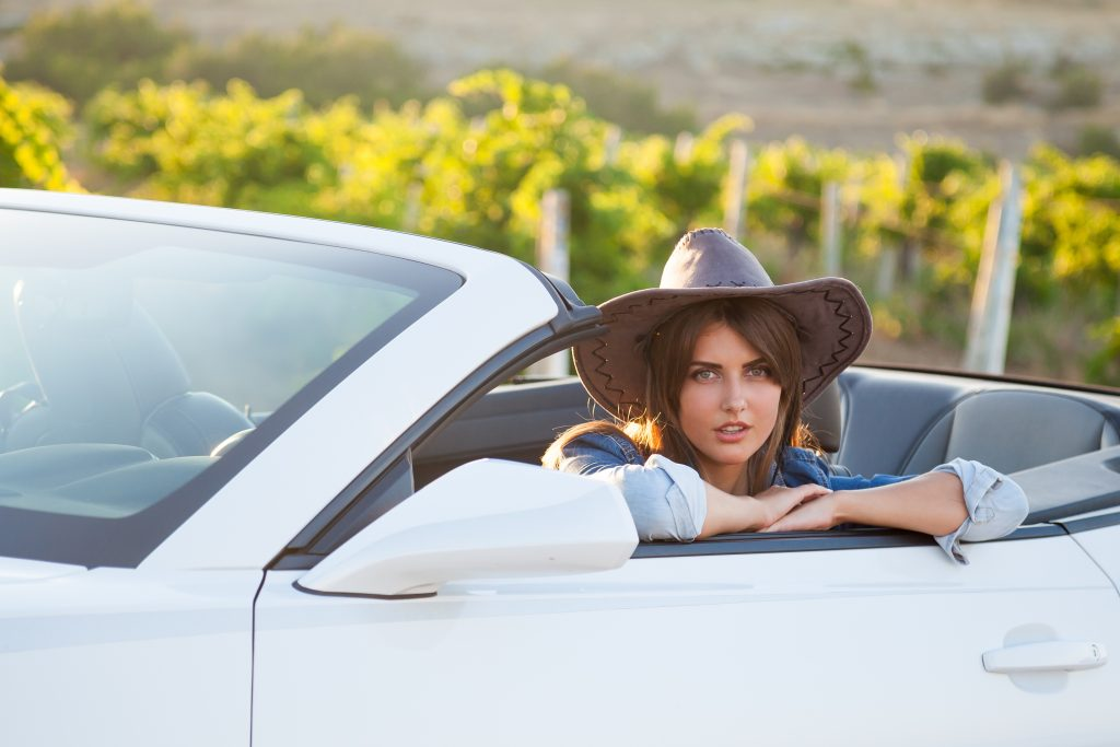 A cowgirl sits in the front seat of a convertible in the Texas country.