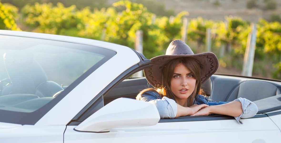 A cowgirl sits in the front seat of a convertible in the country.