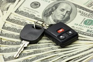 Car keys on top of one hundred dollar bills after getting a car title loan.