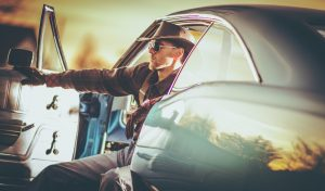 Menacing cowboy sits in the front seat of a muscle car with the door open in Yuma, AZ.