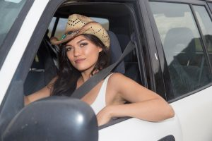 Beautiful cowgirl sits in the front seat of an SUV.