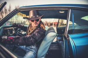 Menacing cowboy sits in the front seat of a muscle car with the door open in Clearwater.