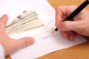 Max Cash Title Loans Michigan title loan application with an envelope of large bills next to it.