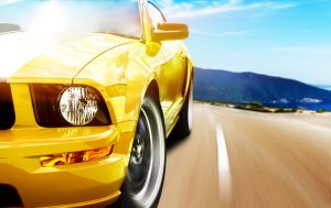 Yellow sports car speeds down an Arizona highway.
