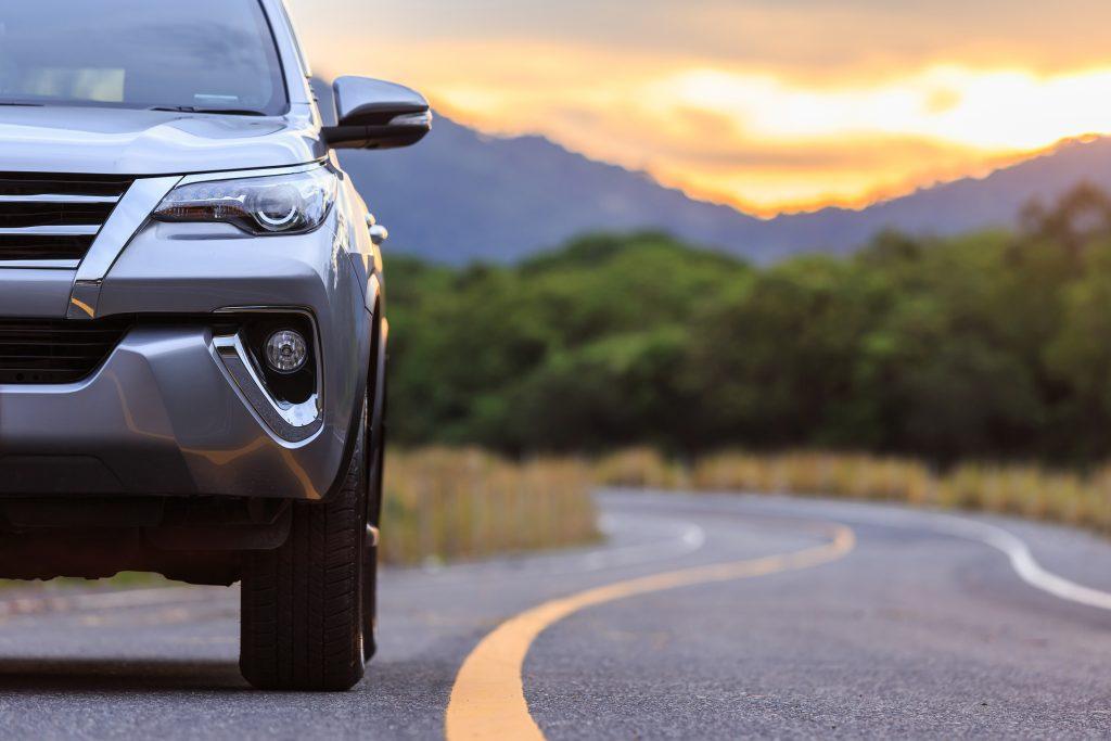 A car drives through the Texas countryside at dusk.