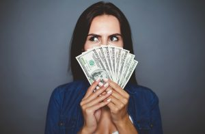 Pretty lady fanning money in front of her face before a grey background after getting title loans
