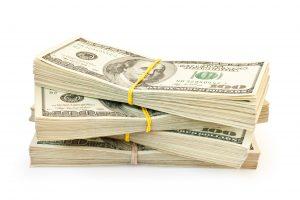 A stack of hundred dollar bills in bundles.
