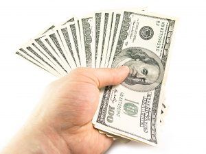 Hundreds of dollars are being fanned out by a man's hand.
