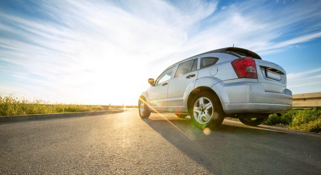 A white sedan drives down a Texas country road during sunrise.