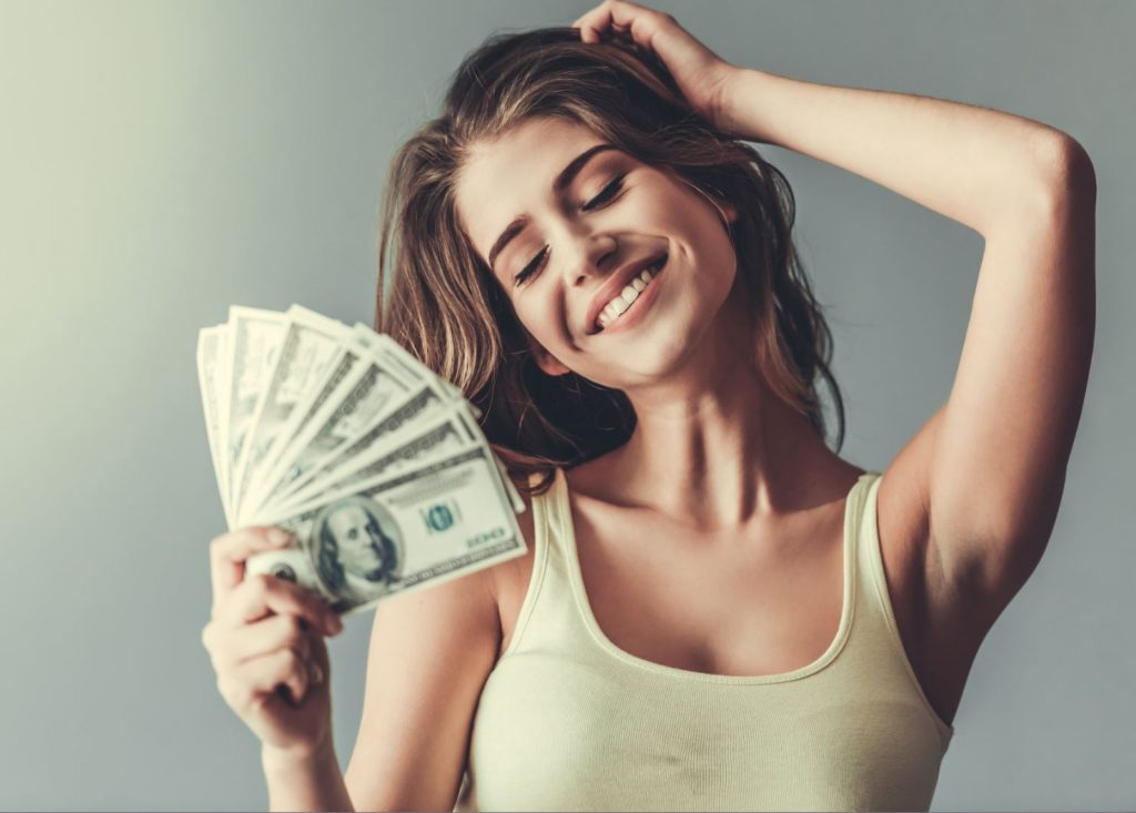 Beautiful woman fans herself with a bunch of one-hundred dollar bills.