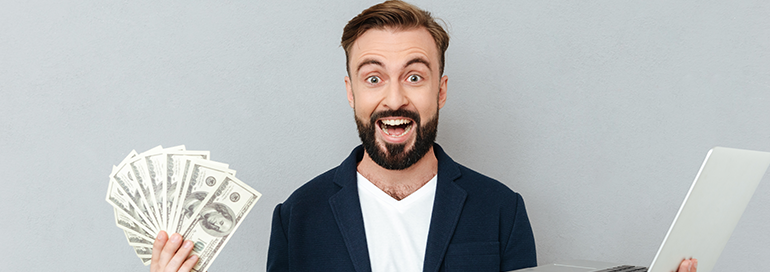Happy Guy with Lots of Cash In one hand and Laptop in another