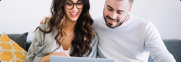 Happy couple using laptop