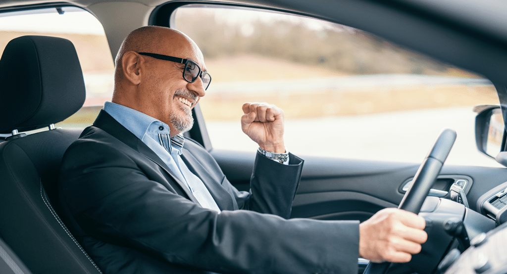 A person driving his car and smiling