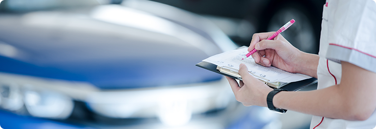 A person filling out the checklist in front of a car