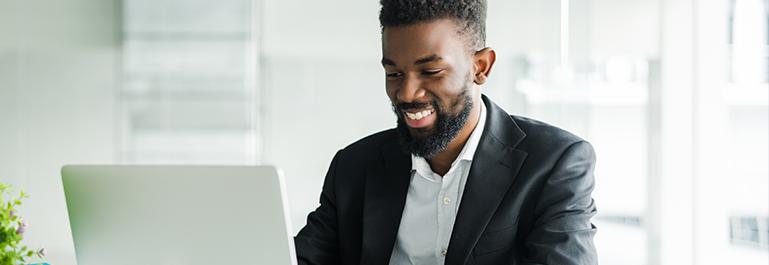 A happy person in formal wear using laptop